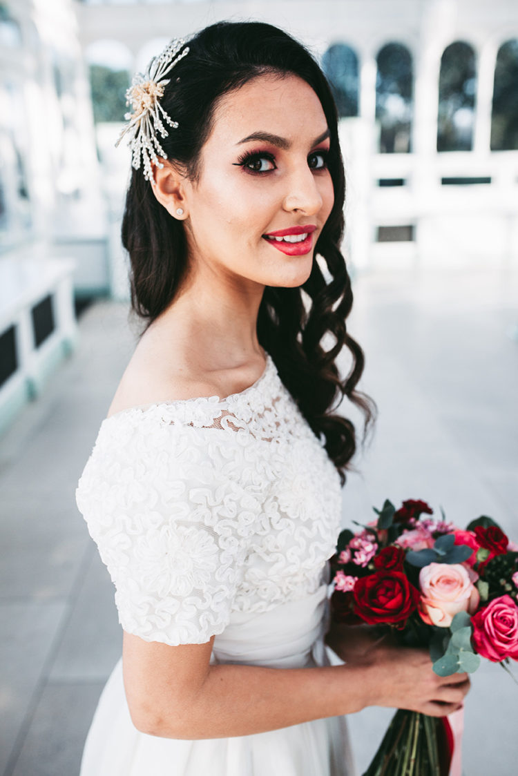 The wedding makeup was done with long lashes, with a bright lipstick and pink shadows