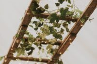 03 a cute wedding decoration of a wooden ladder with lights and greenery for a rustic wedding