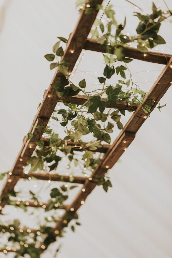 a cute wedding decoration of a wooden ladder with lights and greenery for a rustic wedding