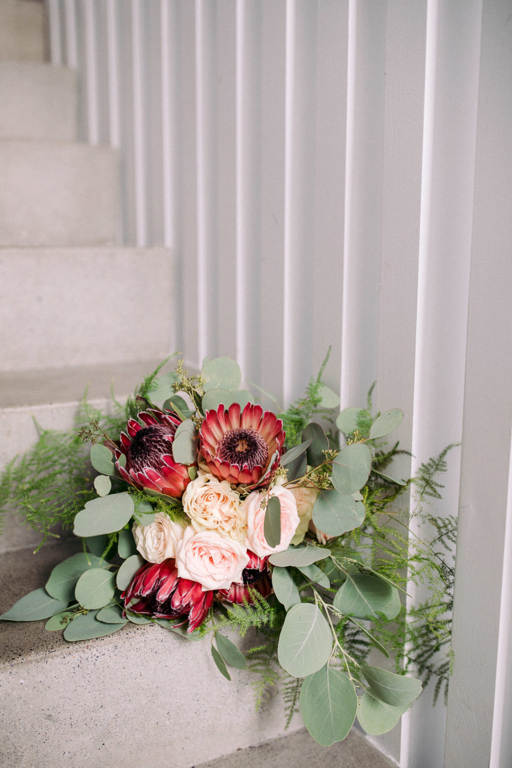 The wedding bouquet was done with blush roses, proteas and greenery