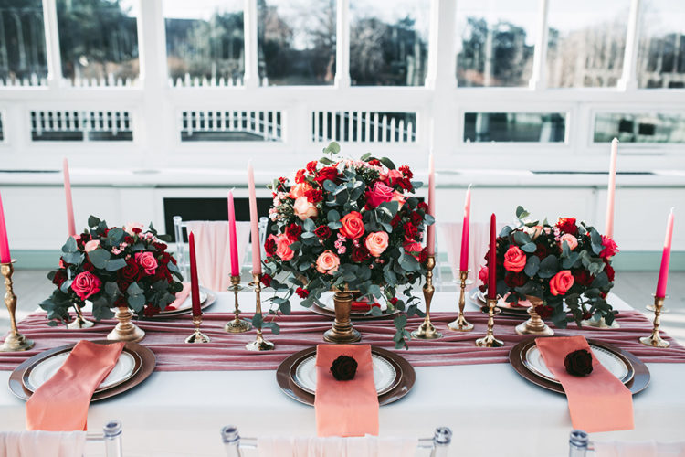 The wedding tablescape was done with a pink velvet runner, pink and red roses and candles plus gold touches