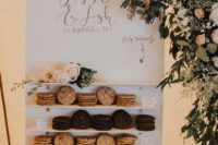 04 a modern small cookie wall with shelves, calligraphy, blush blooms and greenery and tasty cookies