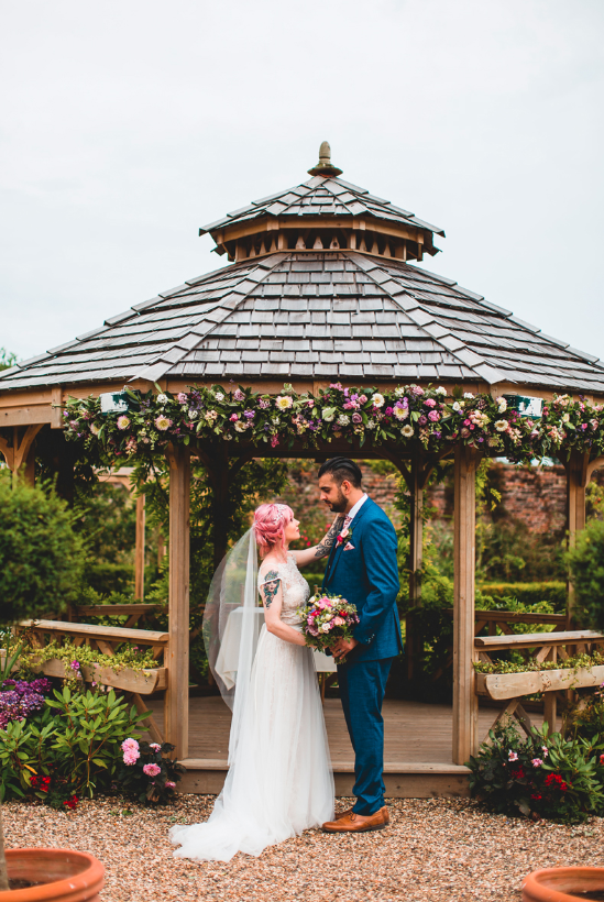 The wedding ceremony took place in a wooden pergola decorated with blush bright blooms