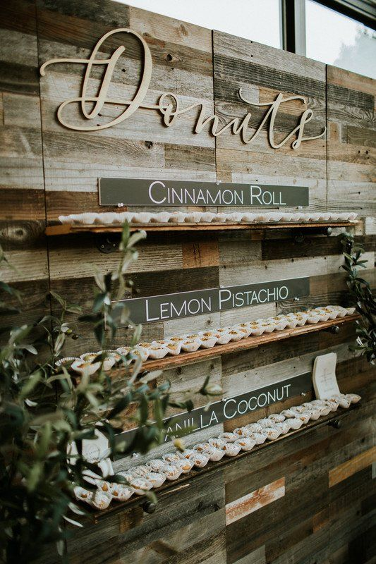 a reclaimed wooden wall with shelves and various delicious donuts is a cool idea for a rustic or farmhouse wedding