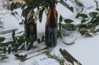 05 lush greenery centerpieces in bottles and a greenery runner make up cool decor for a modern wedding