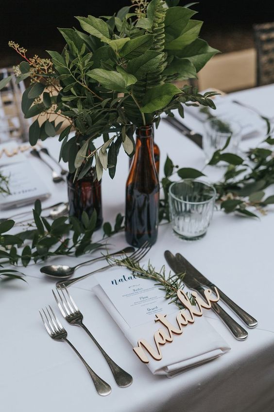 lush greenery centerpieces in bottles and a greenery runner make up cool decor for a modern wedding