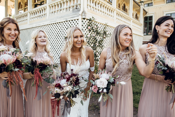 The bridesmaids were wearing blush maxi dresses with lace bodices and pleated skirts