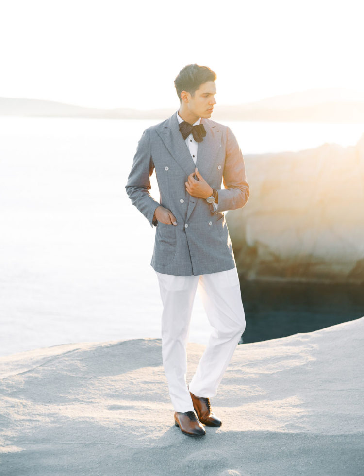 The groom was wearing an island look with white pants, vintage shoes, a grey oversized blazer and a polka dot bow