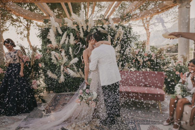 The wedding backdrop was covered with greenery and pampas grass plus calligraphy