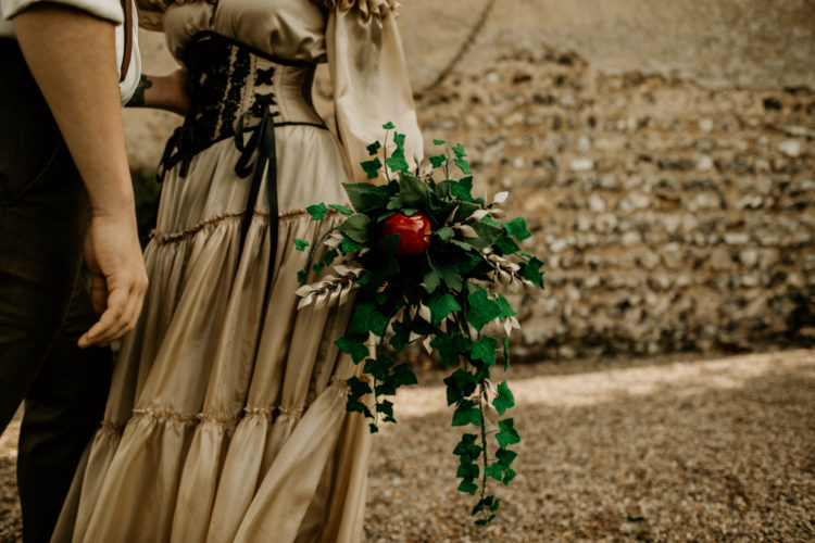 The wedding bouquet was done with greenery and a single red apple