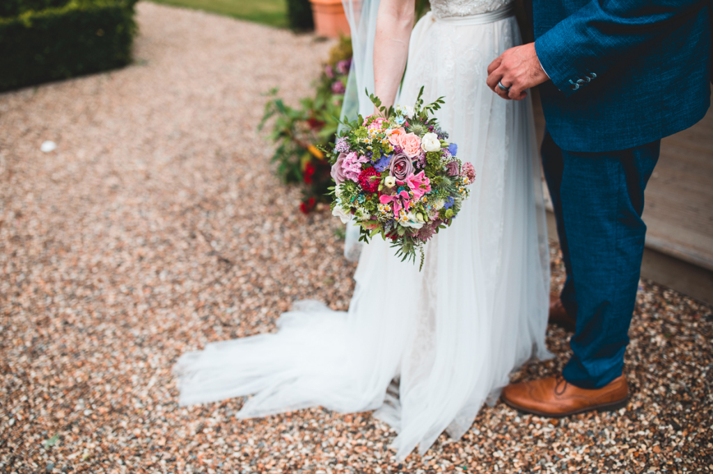 The wedding bouquet was shaped as a ball and was done with purple, pink, red and white blooms and greenery