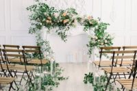 06 a gorgeous wedding ceremony space with greenery on the aisle and greenery and blooms on the faux mantel