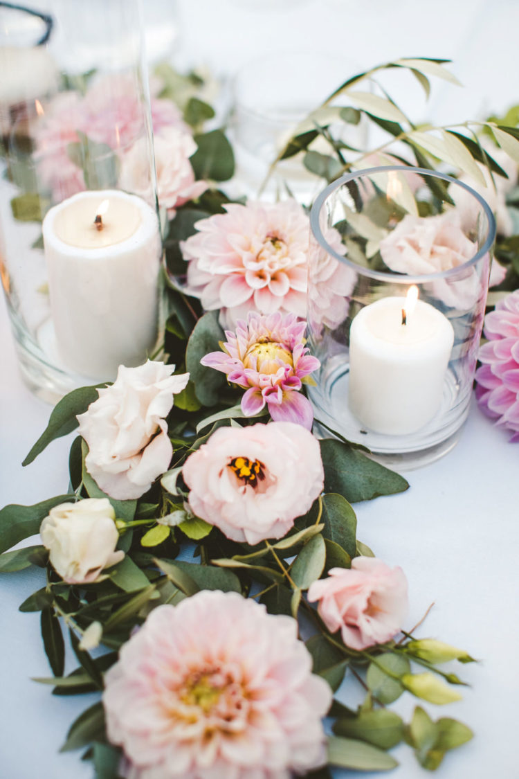 The weddin decor was lush, tender and romantic, with candles and pink blooms