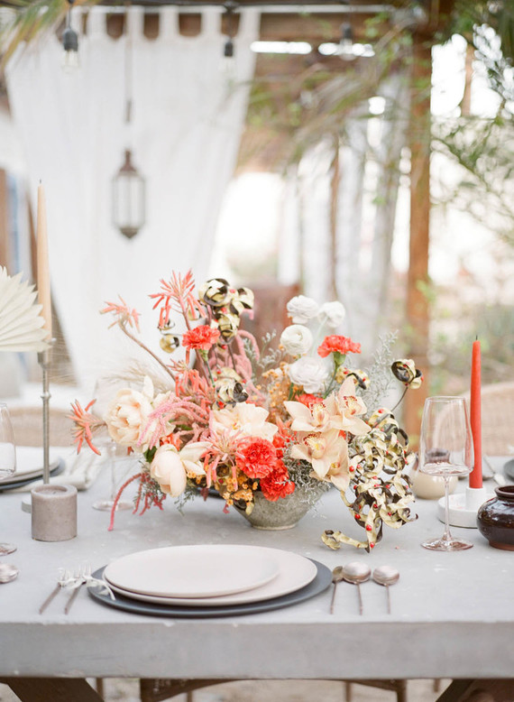 The wedding tablescape was done with concrete candleholders, colorful candles and bold blooms and greenery