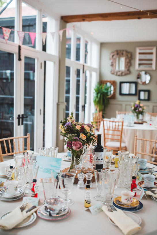 The wedding tablescapes were done with bright blooms, wood slices, and favors were tiny alcohol bottles