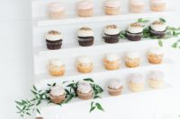 07 a chic cupcake wall in white, with gold calligraphy and fresh greenery is a nice idea for a bridal shower or a wedding