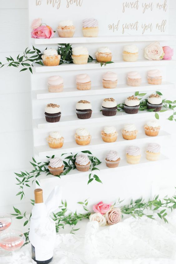 a chic cupcake wall in white, with gold calligraphy and fresh greenery is a nice idea for a bridal shower or a wedding