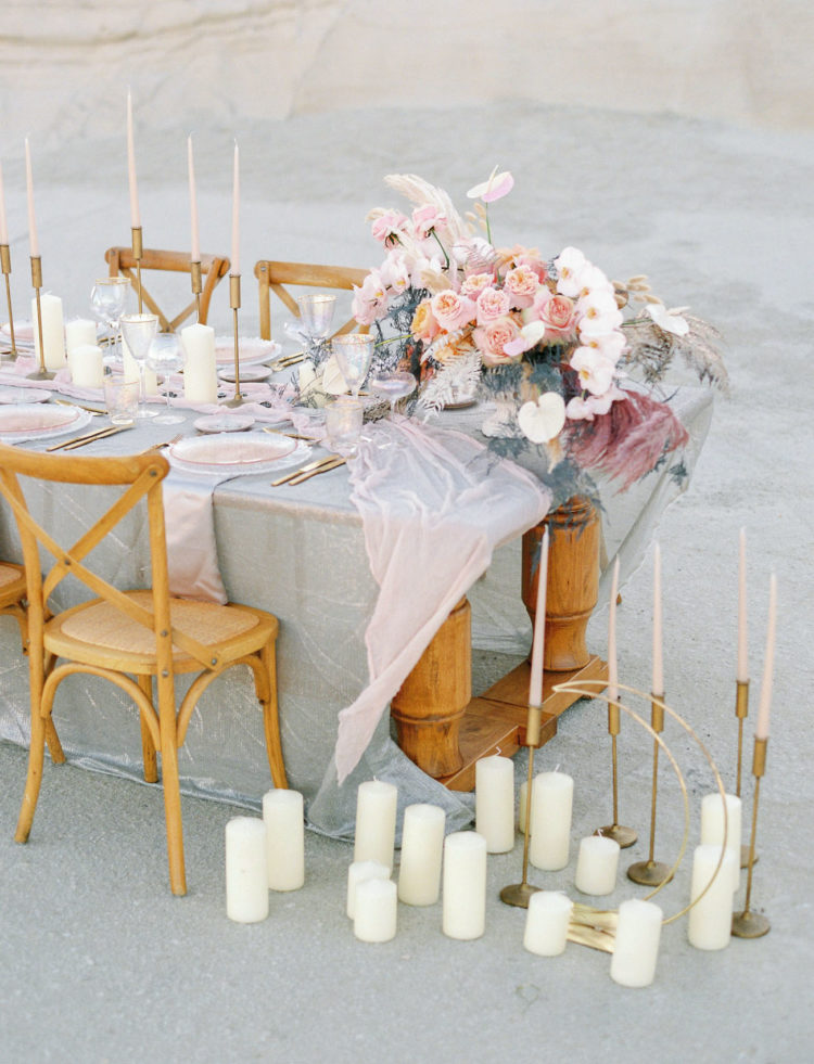 The table was decorated with delicate linens, pastel florals, candles and pink glass chargers