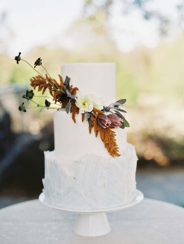 The chic wedding cake was done with white chocolate shards, dramatic blooms and greenery