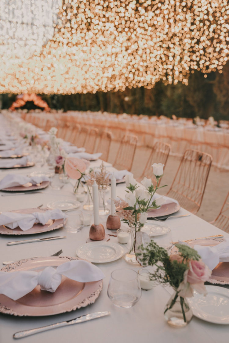 The tables were decorated with pink chargers, copper candle holders, white and pink flowers and white napkins