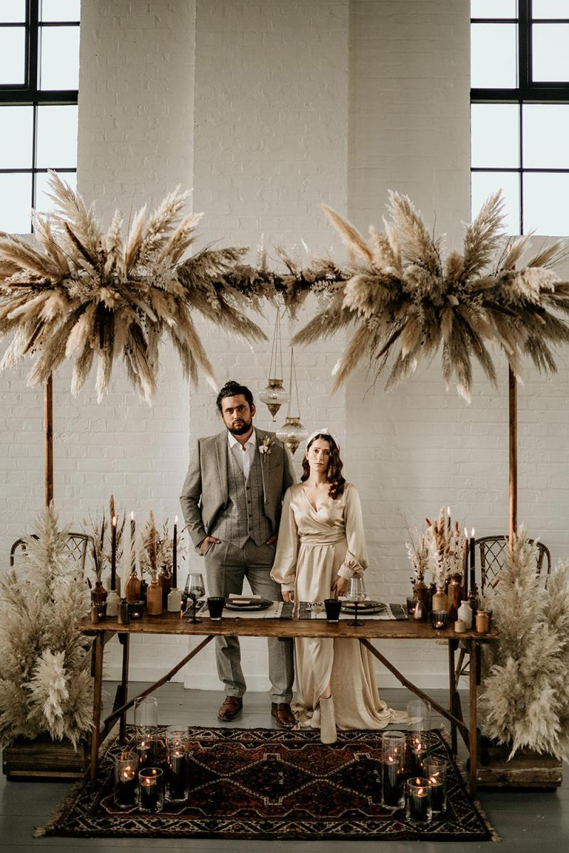 The wedding reception was done with pampas grass, black candles, terracotta vases