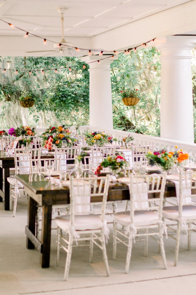 The wedding tablescapes were done with uncovered tables, colorful blooms and greenery and neutral napkins