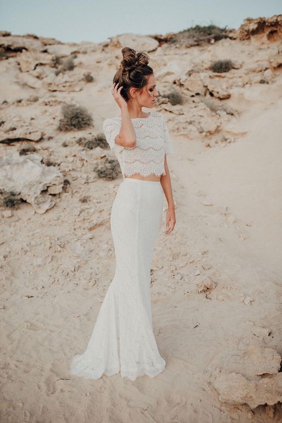 a modern yet romantic bridal separate of a lace crop top with short sleeves and a high neckline and a matching lace mermaid skirt