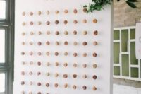 09 a stylish wedidng donut wall with mini donuts, letters, lilac blooms and greenery for decor is a very modern and fresh idea