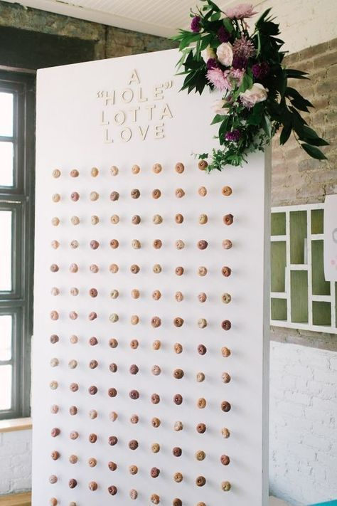 a stylish wedidng donut wall with mini donuts, letters, lilac blooms and greenery for decor is a very modern and fresh idea