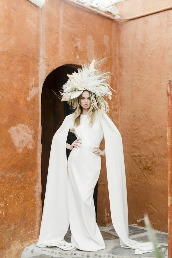 The second wedding dress was minimalist, with cape sleeves and a statement dried flower crown