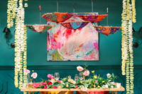 10 The sweetheart table featured greenery and bold blooms, colorful umbrellas and an artwork
