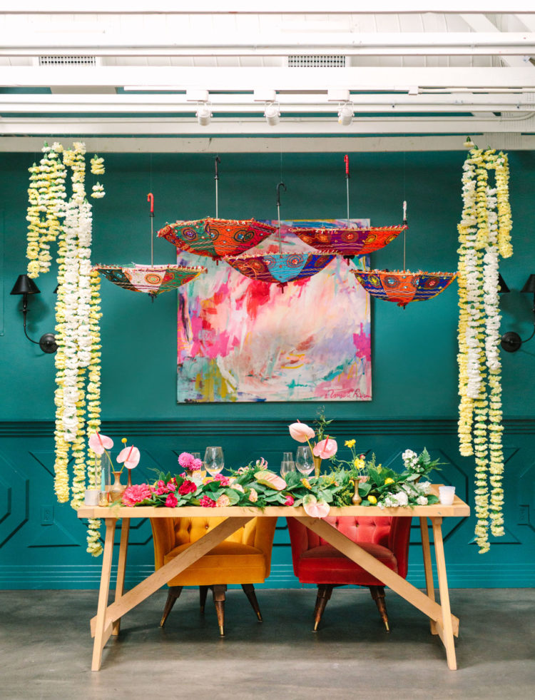 The sweetheart table featured greenery and bold blooms, colorful umbrellas and an artwork