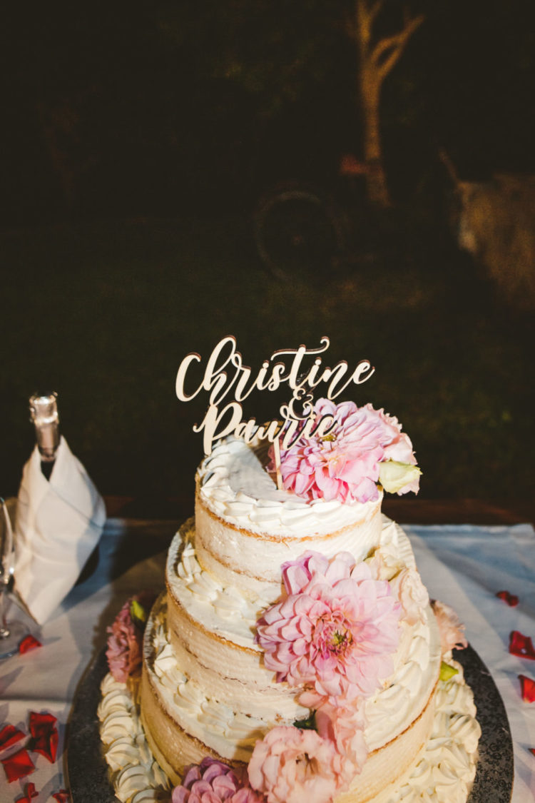 The wedding cake was a naked one with pink flowers and a calligraphy topper