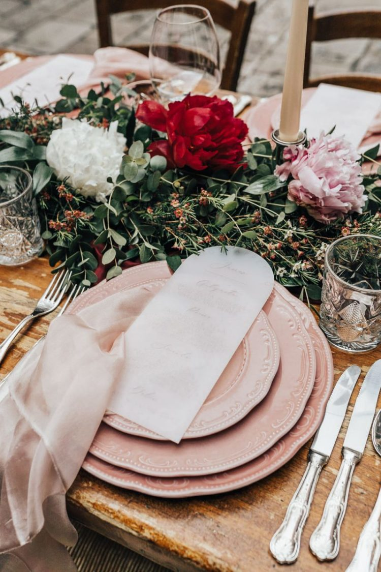The wedding tablescape was done with pink plates, lush greenery and bold blooms
