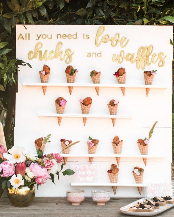 an ice cream cone wall with mini shelves, gold calligraphy and soem bright blooms and greenery in a vase