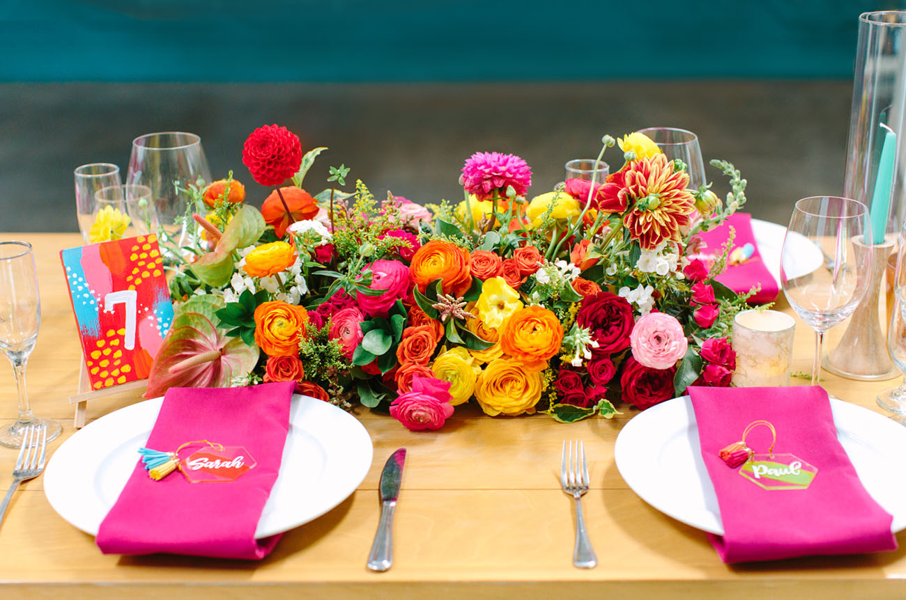 Bodl florals and greeneyr, bright napkins and cards were present on each table