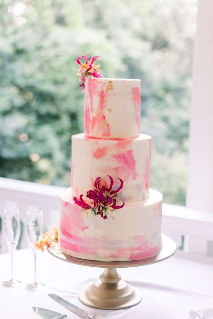 The wedding cake was a watercolro pink one with gold leaf and topped with bright blooms