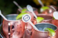 11 signature wedding drinks in copper mugs and with wooden drink stirrers with monograms