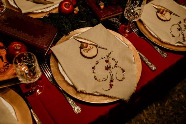 The wedding tablescape was done with apples, acorns, wood slicesm embroidered napkins and glasses