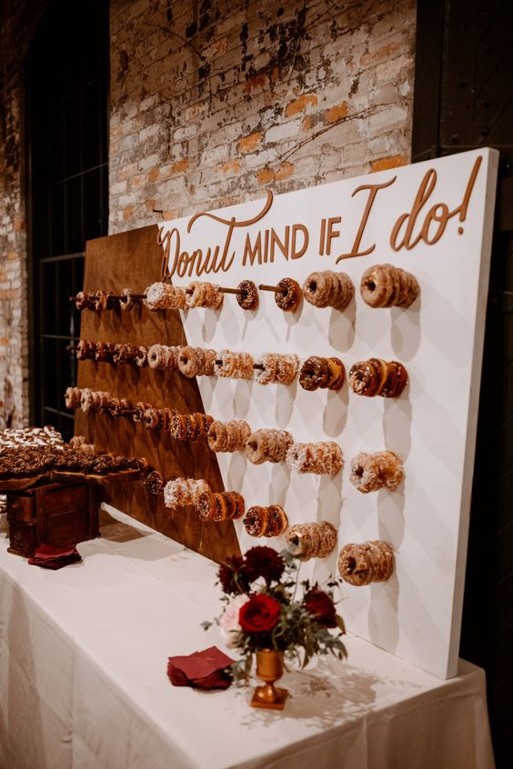 a color block donut wall with copper calligraphy and donut holders is a fresh and modern idea to show off your desserts