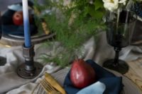 12 a moody tablescape done with a grey table runner, grey plates, a sheer charger with a gold rim, ombre blue candles and black glasses