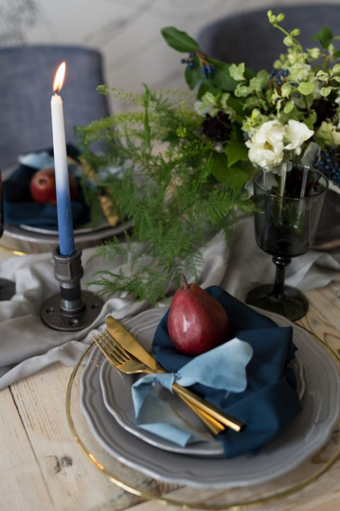 a moody tablescape done with a grey table runner, grey plates, a sheer charger with a gold rim, ombre blue candles and black glasses