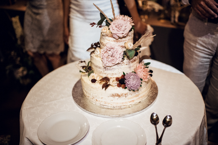 The naked wedding cake was decorated with pastel blooms, berries and greenery