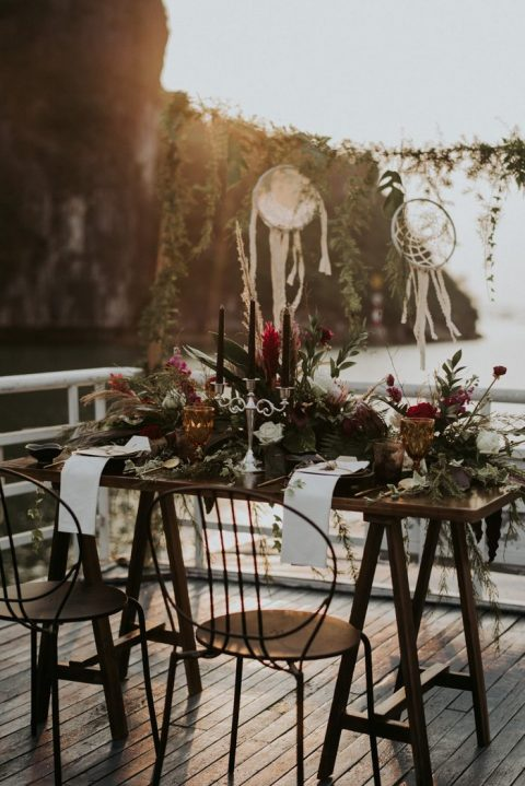 a lush wedding tablescape with blooms, greenery, pampas grass, black candles and amber glasses for a boho feel