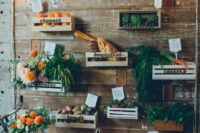 13 a reclaimed wooden wall with crates and various flowers, vegetables, fruits, lights and letters for a farm to table wedding