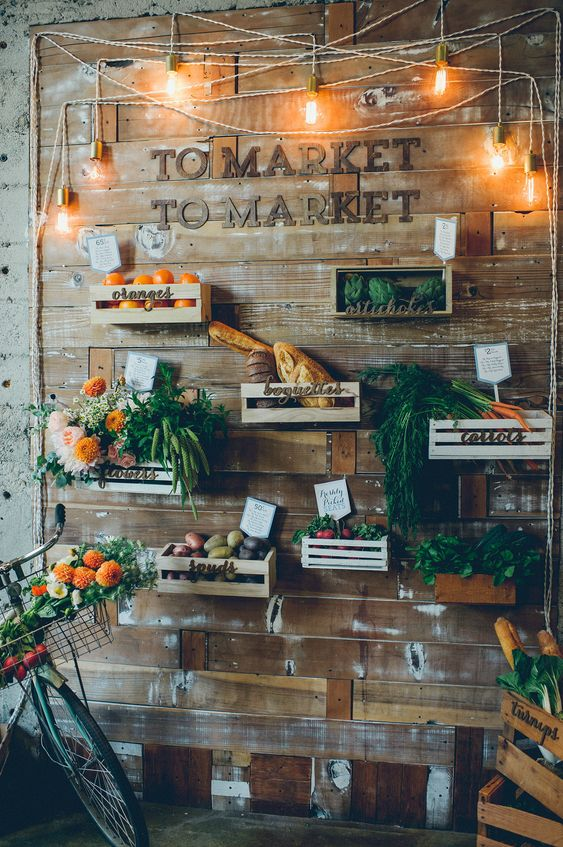 a reclaimed wooden wall with crates and various flowers, vegetables, fruits, lights and letters for a farm to table wedding