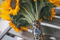 13 a sunflower wedding bouquet with a leopard print wrap and a tiny birdie for something blue