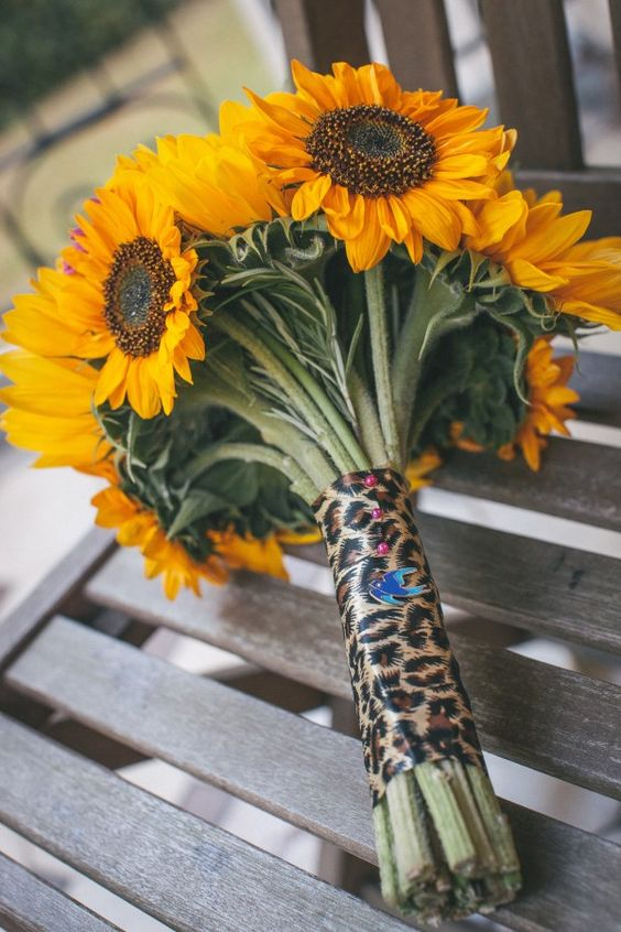 a sunflower wedding bouquet with a leopard print wrap and a tiny birdie for something blue