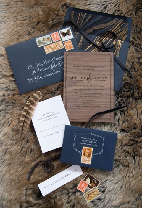 a refined wedding invitation suite done with wood grain, navy envelopes and feathers