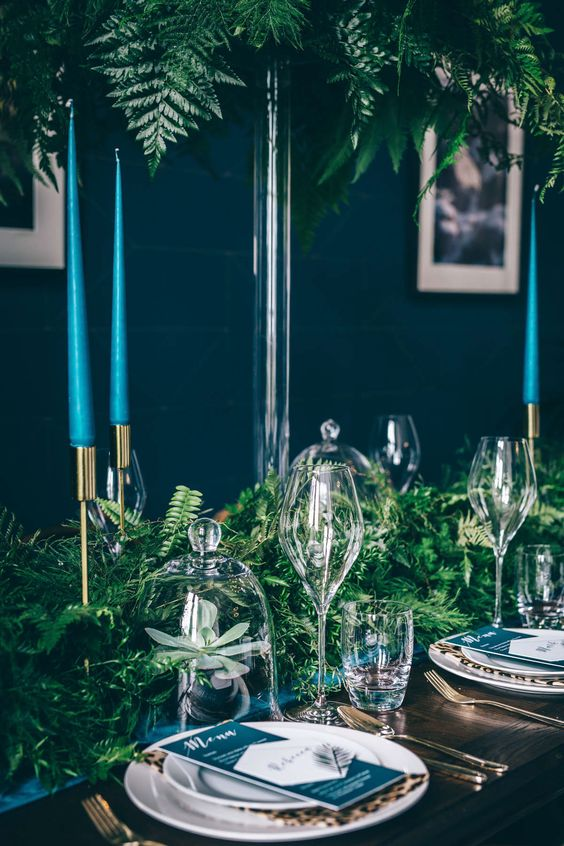 a teal, turquoise wedidng tablescape with leopard print napkins, tall candles and a lush greenery table runner
